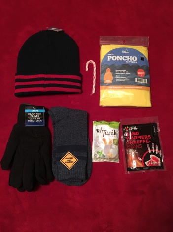 Men's toque, gloves, socks, poncho, 2 hand warmer packet & candy cane. (donated tea/coffee packet).