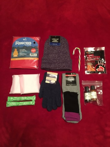 Women's poncho, feminine hygiene products gloves, socks, 2 hand warmers & candy cane. (donated care products).
